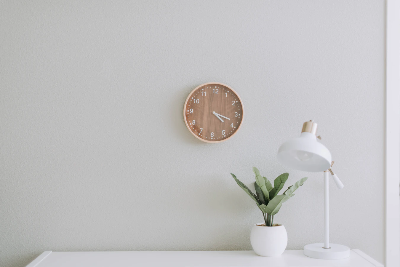 plain wall with clock and plant on desk